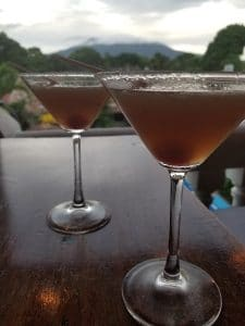 close up of martinis with cloud capped Mombacho volcano in the background